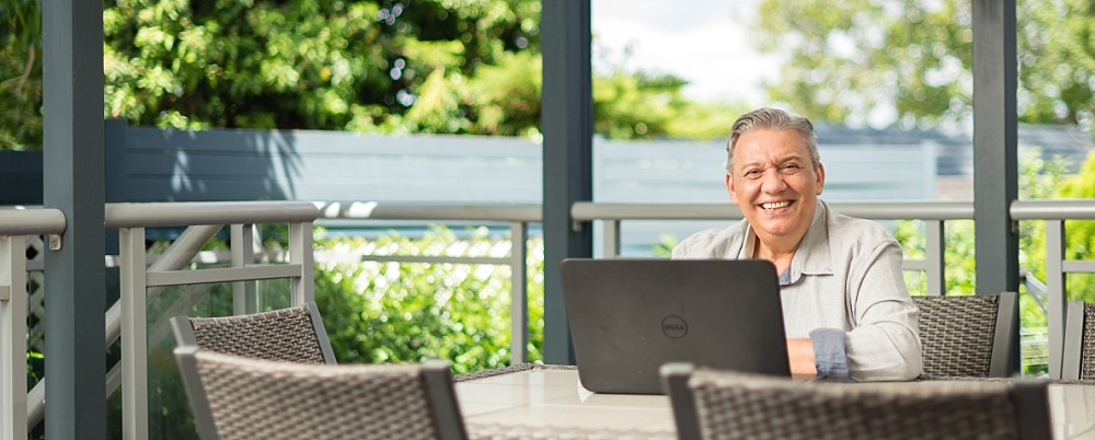 Sydney Bookkeeper working on laptop at outdoor table with trees in background