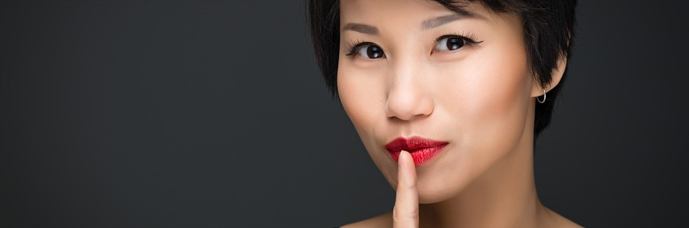 Asian female beauty headshot with finger to lips