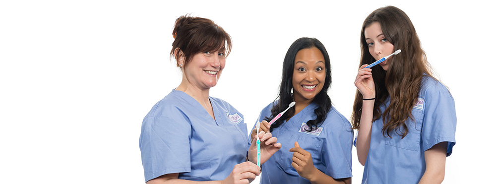 3 women in blue scrubs holding toothbrushes in Sydney studio
