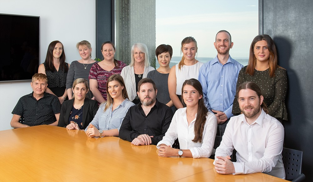 Professional staff team photograph at conference table in Sydney CBD highrise building
