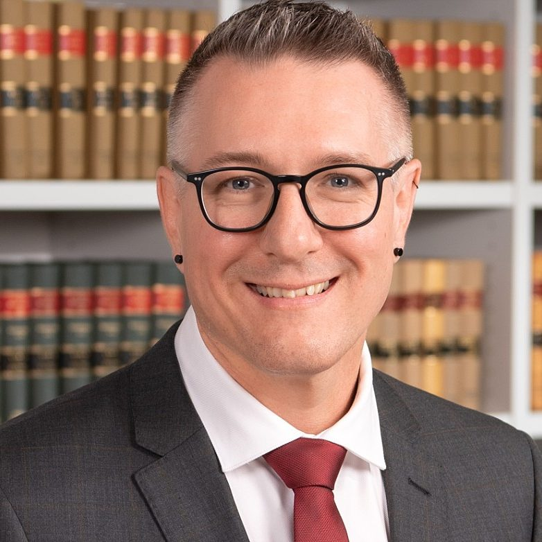 Headshot of Lawyer in front of bookshelf in Sydney