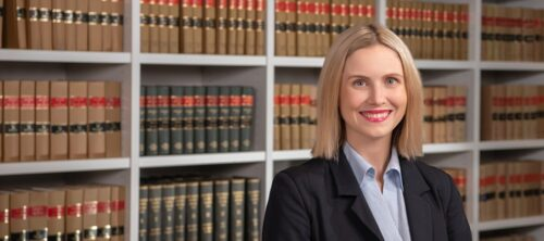 Female lawyer standing in front of law books in Sydney office