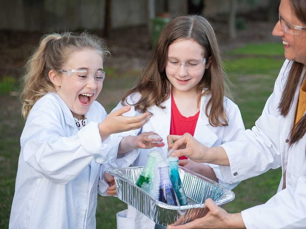 Two girls experimenting with science wearing labcoats