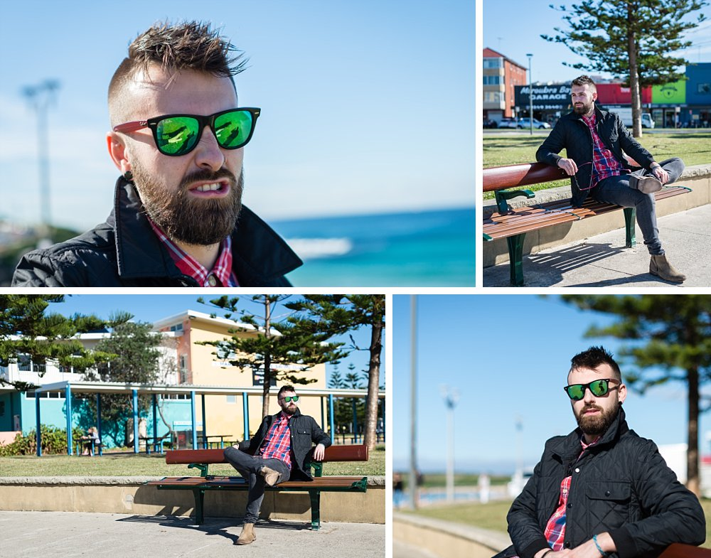 Caucasian man with short hair, beard, sunglasses sitting casually at Maroubra beach