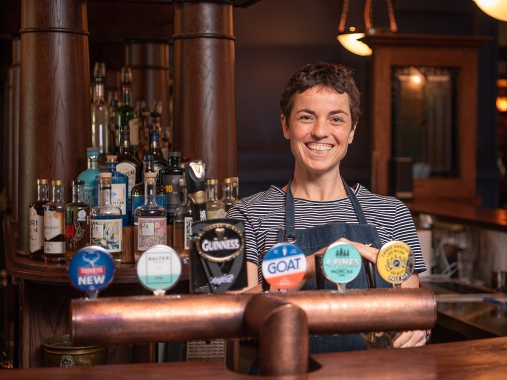 Female bartender behind bar with beer taps