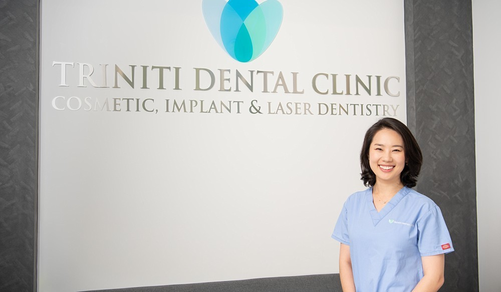 Female dental surgeon standing in front of clinic sign